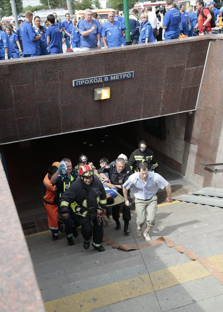 Paramedics, a police officer and a voluenteer carry an injured man out from a subway station after a rush-hour subway train derailment in Moscow, Russia, on Tuesday, July 15, 2014. A rush-hour subway train derailed in Moscow Tuesday, killing about 20 people and injuring at least 106, emergency officials said. Several cars left the track in the tunnel after a power surge triggered an alarm, which caused the train to stop abruptly. (Photo by Ivan Sekretarev/AP Photo)