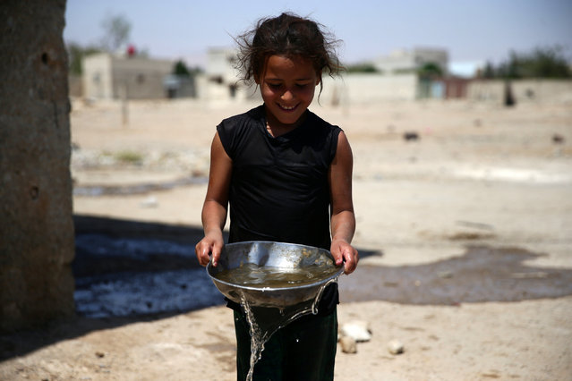 A girl carries a bowl filled with water, in the rebel held besieged town of Douma, eastern Damascus suburb of Ghouta, Syria, June 23, 2016. (Photo by Bassam Khabieh/Reuters)