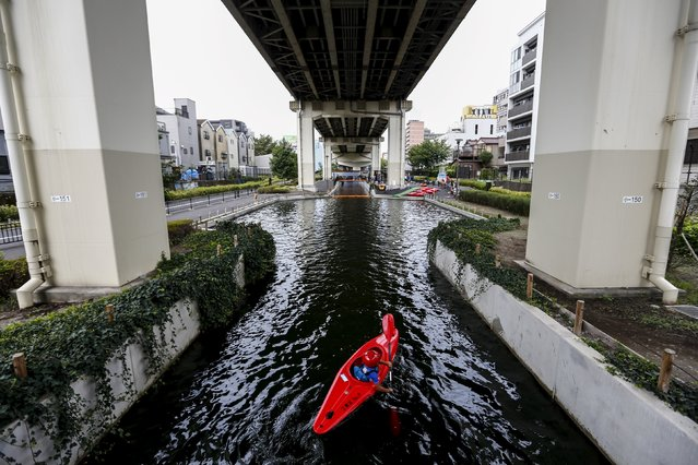 A boy paddles on a hot summer day in a canoe through a canal underneath the Keiyo highway that runs on stilts through eastern Tokyo August 12, 2015. (Photo by Thomas Peter/Reuters)