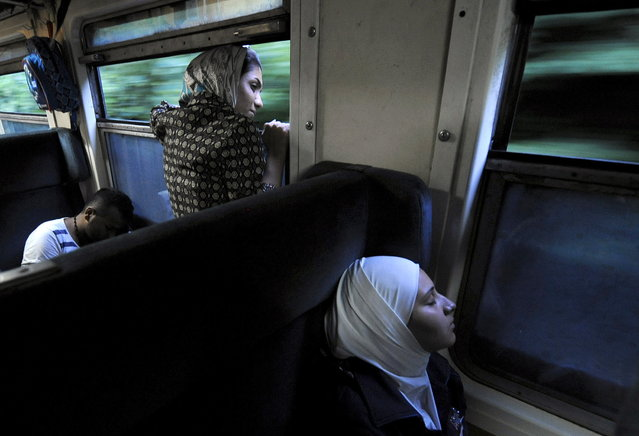 A woman looks out of the window as she travels on a train through Macedonia July 31, 2015. (Photo by Ognen Teofilovski/Reuters)