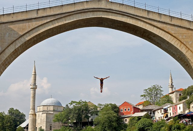 A competitor jump off the Old Bridge during the Red Bull Cliff Diving Competition in Mostar, Bosnia and Herzegovina on August 15, 2015. (Photo by Dado Ruvic/Reuters)