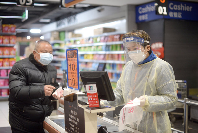 A cashier in a plastic gown works at the checkout of a supermarket in Wuhan, the epicenter of the novel coronavirus outbreak, in central China's Hubei province Monday, February 10, 2020. (Photo credit should read Feature China/Barcroft Media via Getty Images)