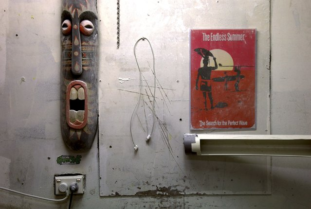 A surfing movie poster, a phone cable and a wood carving adorn the wall of a surfboard workshop owned by Craig 'Buddha' Cummins where he installs shark repellent devices in Sydney, Australia, August 14, 2015. (Photo by David Gray/Reuters)