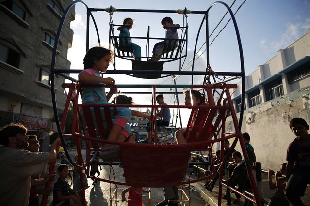 Palestinian children play on a mini ferris wheel along a street in Beit Lahiya in the northern Gaza Strip July 29, 2014. Israel knocked out Gaza's only power plant, flattened the home of its Islamist Hamas political leader and pounded dozens of other high-profile targets in the enclave on Tuesday, with no end in sight to more than three weeks of conflict. More than 1,100 Gazans, most of them civilians, have been killed in the conflict. On the Israeli side, 53 soldiers have been killed as well as three civilians. (Photo by Finbarr O'Reilly/Reuters)
