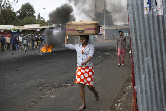 A Kenyan woman carrying a suitcase on her head walks past a small group of demonstrators in Nairobi's Kibera slum Monday, August 14, 2017. Kenyan opposition leader Raila Odinga urged his supporters to skip work on Monday to protest what he charged were rigged elections that gave victory to President Uhuru Kenyatta. The government denounced violent demonstrations as unlawful and urged Kenyans to return to their jobs. (Photo by Jerome Delay/AP Photo)