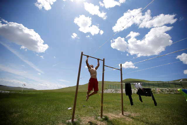A training partner of Mongolia's Olympic wrestler team does pull-ups after a daily training session outside the Mongolia Women's National Wrestling Team training centre in Bayanzurkh district of Ulaanbaatar, Mongolia, July 1, 2016. (Photo by Jason Lee/Reuters)