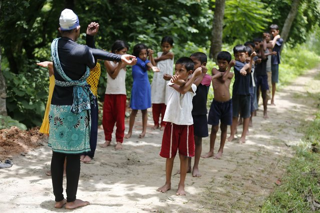 In this July 14, 2017 photo, Bangladeshi children attend a warm up session before a swimming practice in the Shishu Polli Plus area in Sreepur village, near Dhaka, Bangladesh. (Photo by A.M. Ahad/AP Photo)