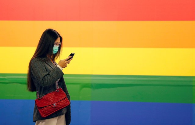 A woman in a face mask uses her phone in Porta Venezia subway in Milan, as the country is hit by the coronavirus outbreak, Italy on February 25, 2020. (Photo by Yara Nardi/Reuters)