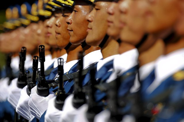 Soldiers of China's People's Liberation Army march with their weapons during a training session for a military parade to mark the 70th anniversary of the end of World War Two, at a military base in Beijing, China, August 22, 2015. Troops from at least 10 countries including Russia and Kazakhstan will join an unprecedented military parade in Beijing next month to commemorate China's victory over Japan during World War Two, Chinese officials said. (Photo by Damir Sagolj/Reuters)