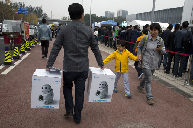 A man walks with boxes of companion robots outside the venue for the World Robot Conference in Beijing, China, Friday, October 21, 2016. (Photo by Ng Han Guan/AP Photo)