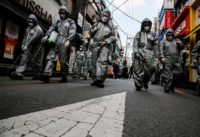 South Korean soldiers in protective gear sanitize a shopping street in Seoul, South Korea, March 4, 2020. (Photo by Heo Ran/Reuters)