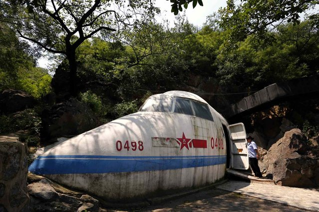 Shaped in the form of an aeroplane, an attendant opens the door to the entrance of a cave that was once the headquarters of former Chinese Communist military leader Lin Biao, located in mountains on the outskirts of Beijing on July 16, 2012. (Photo by David Gray/Reuters Photo)