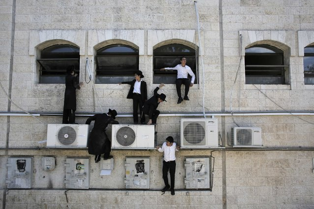 Ultra-Orthodox Jewish boys climb down a wall near the scene of a suspected attack in Jerusalem August 4, 2014. A Palestinian killed an Israeli and overturned a bus with a construction vehicle on Monday and a gunman wounded a soldier in attacks in Jerusalem that appeared to be a backlash against Israel's Gaza war. There were no passengers on the bus, in an ultra-Orthodox Jewish neighbourhood of the city. (Photo by Ammar Awad/Reuters)