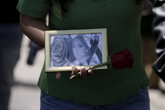 A picture of Andrea Alvarez, whose death is being investigated as a femicide, is displayed during a rally at her funeral march in La Paz, Bolivia August 22, 2015. (Photo by David Mercado/Reuters)