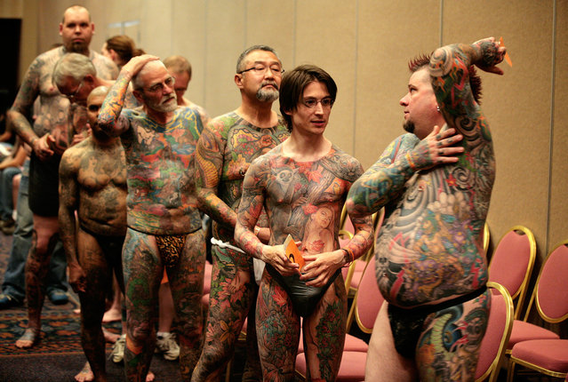 Jeff Bitting (right), from St Augustine, Florida, speaks backstage with fellow full-body tattoo contestants before judging at the National Tattoo Association Convention in Cincinnati, Ohio, on April 13, 2012. In his 33 years of getting tattoos, Bitting says he has had about 500 hours of work and will complete his other leg in his bid to win more full-body contests. (Photo by Larry Downing/Reuters)