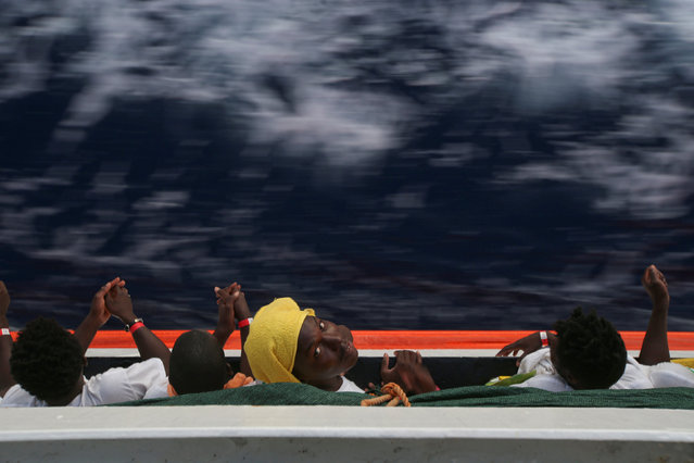 Migrants rest on the MV Aquarius rescue ship after being rescued by SOS Mediterranee organisation during a search and rescue (SAR) operation in the Mediterranean Sea, off the Libyan Coast, September 15, 2017. (Photo by Tony Gentile/Reuters)