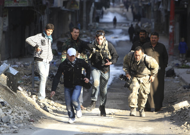 Journalists Bryn Karcha (C) of Canada and Toshifumi Fujimoto (R) of Japan run for cover next to an unidentified fixer in a street in Aleppo's district of Salaheddine December 29, 2012. (Photo by Muzaffar Salman/Reuters)