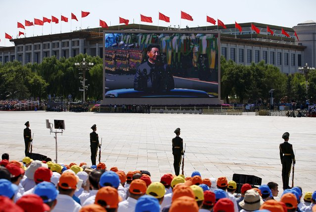 A screen displays Chinese President Xi Jinping reviewing the army at the Tiananmen Square, at the beginning of the military parade marking the 70th anniversary of the end of World War Two, in Beijing, China, September 3, 2015. (Photo by Damir Sagolj/Reuters)