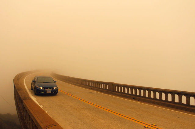 Smoke from the Soberanes Fire combined with a marine layer reduces visibility over Bixby Bridge on State Route 1 north of Big Sur, California, U.S. July 26, 2016. (Photo by Michael Fiala/Reuters)