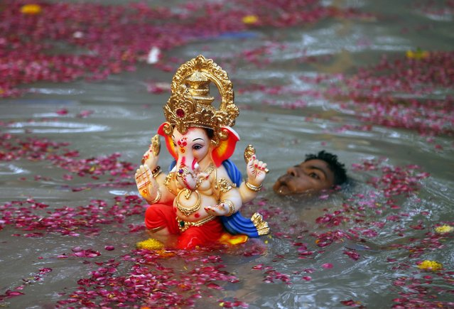 An Indian devotee carries an idol of elephant-headed Hindu God Ganesha for immersion in a water body on the second day of the ten-day Ganesh festival in Mumbai, India, Saturday, August 30, 2014. (Photo by Rajanish Kakade/AP Photo)