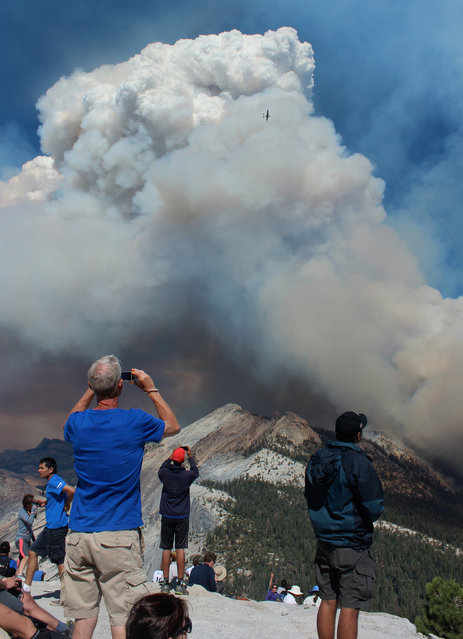 In this Sunday, September 7, 2014 photo provided by Rachel Kirk, hikers take photos of smoke from a fire rising above Little Yosemite Valley near Yosemite National Park, Calif. (Photo by Rachel Kirk/AP Photo)