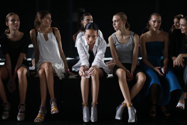 Jing Wen, center, of Guangzhou, China, waits to rehearse with other models before the Prabal Gurung Spring 2015 collection show Saturday, September 6, 2014, during Fashion Week in New York. Jing Wen, 19, began modeling at age 17. She says that as a little girl, she loved the idea of modeling, but never dreamed that she would end up walking runways internationally. Although her mother and sister are back in China, she doesn't often suffer from homesickness. (Photo by Jason DeCrow/AP Photo)