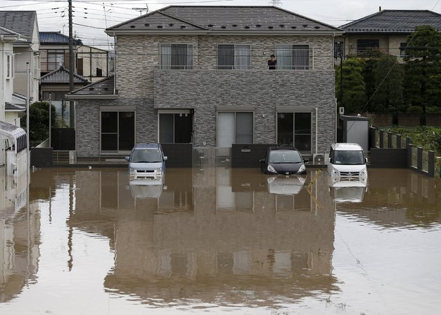 A man stands on the balcony of a house at a residential area flooded by the Kinugawa river, caused by typhoon Etau, in Joso, Ibaraki prefecture, Japan, September 10, 2015. (Photo by Issei Kato/Reuters)