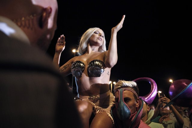 """Singer Lady Gaga performs for the crowd upon her arrival at the Athens' Eleftherios Venizelos airport September 17, 2014. Lady Gaga will perform in Athens on Friday during her """"ArtRave: The Artpop Ball"""" world tour. (Photo byAlkis Konstantinidis /Reuters)"""