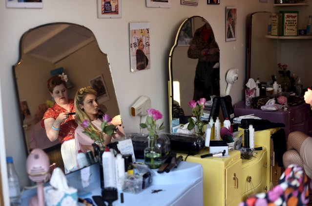 Visitors and car enthusiasts are seen in a hair salon at the Goodwood Revival historic motor racing festival in Goodwood, near Chichester in south England, Britain, September 11, 2015. (Photo by Toby Melville/Reuters)
