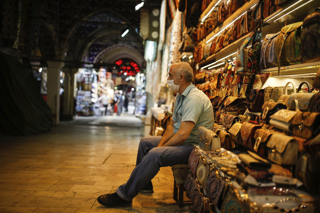 A vendor, wearing a protective face mask against the spread of coronavirus, waits for customers at the iconic 15th century Grand Bazaar in Istanbul as it reopens, Monday June 1, 2020, following weeks of closure due to the coronavirus pandemic. Turkish Airlines resumed limited domestic flights, restaurants welcomed sit-in customers and beaches and museums reopened as Turkey's broadest easing of coronavirus restrictions came into effect following a slowdown in confirmed COVID-19 infections and deaths in the country. (Photo by Emrah Gurel/AP Photo)