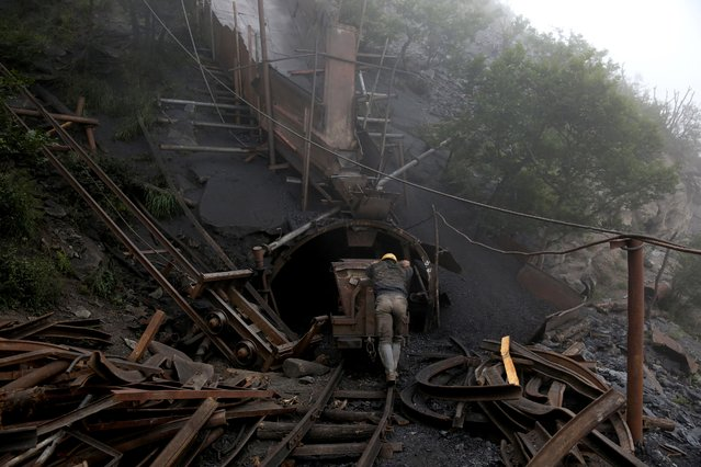 In this Thursday, May 8, 2014 photo, an Iranian coal miner pushes an old metal cart to be loaded with coal at a mine near the city of Zirab 212 kilometers (132 miles) northeast of the capital Tehran on a mountain in Mazandaran province, Iran. A miner said they move up to 100 tons a day. (Photo by Ebrahim Noroozi/AP Photo)