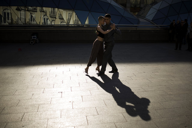 An Argentinian couple cast their shadow on the ground as they dance tango music for money at Sol square in downtown Madrid, Friday, November 17, 2017. (Photo by Francisco Seco/AP Photo)