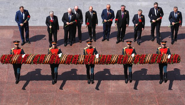 This handout picture provided by Host photo agency shows Russian President Vladimir Putin and the heads of state invited for a military parade, which marks the 75th anniversary of the Soviet victory over Nazi Germany in World War Two, attending a flower-laying ceremony at the Tomb of the Unknown Soldier by the Kremlin Wall in downtown Moscow on June 24, 2020. The parade, usually held on May 9, was postponed this year because of the coronavirus pandemic. (Photo by Alexey Filippov/AFP Photo)