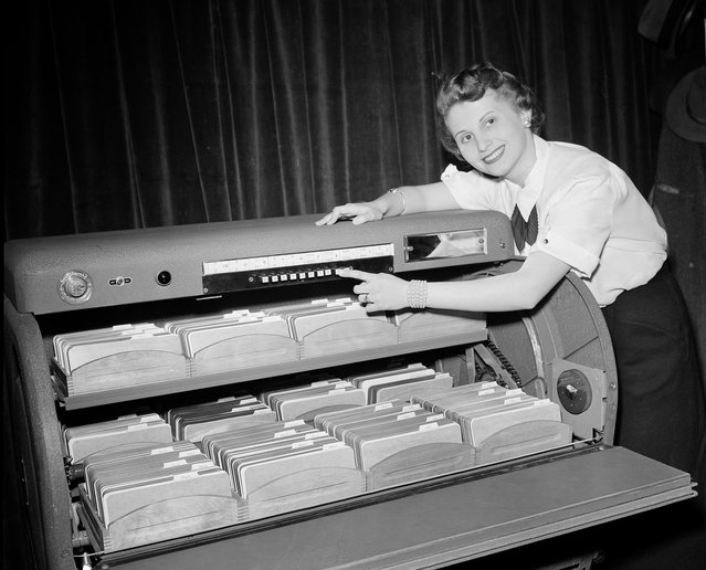 """Barbara Johnson of Chicago pushes one of ten buttons that puts one of the card cradles in place in one of the new motorized card-finding systems shown during the 13th Annual Chicago Business Show, March 3, 1952. The unit contains about 82,000 tabulation cards. Called """"Simplafind"""", it is a product of the Simpla Research and Manufacturing Co., Inc., of New York. The company was one of 77 manufacturers of business machine equipment to display their products at the Conrad Hilton Hotel in Chicago. (Photo by Edward Kitch/AP Photo)"""