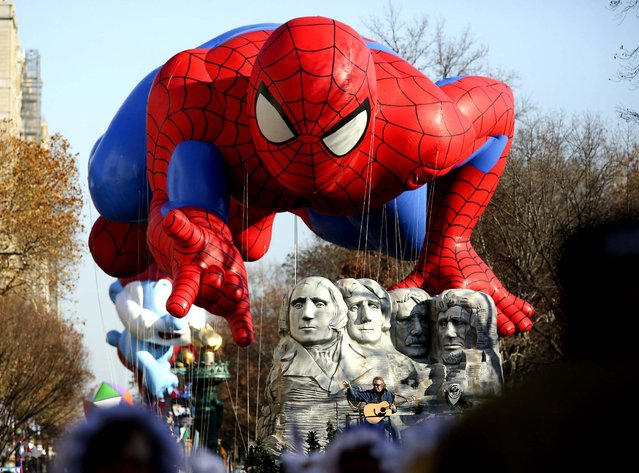 The Spiderman balloon floats over Don McLean during the 86th annual Macy's Thanksgiving Day Parade in New York. (Photo by Suzanne DeChillo/The New York Times)