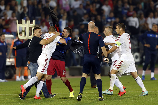A fight breaks out on the pitch between Serbian fans and Albanian national team players, with from right, Albania's Lorik Cana, Albania's Ansi Agolli, match official, 3rd left Serbia's Nenad Tomovic holding Albanian flag, Albania's Bekim Balaj, and soccer fan at left, during the Euro 2016 Group I qualifying match between Serbia and Albania, at the Partizan stadium in Belgrade, Serbia, Tuesday, October 14, 2014. (Photo by Marko Drobnjakovic/AP Photo)