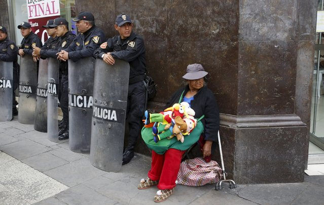 Street vendor Laura Chikasaka Mamani sells puppets next to Peruvian anti-riot police in downtown Lima, September 23, 2015. (Photo by Mariana Bazo/Reuters)