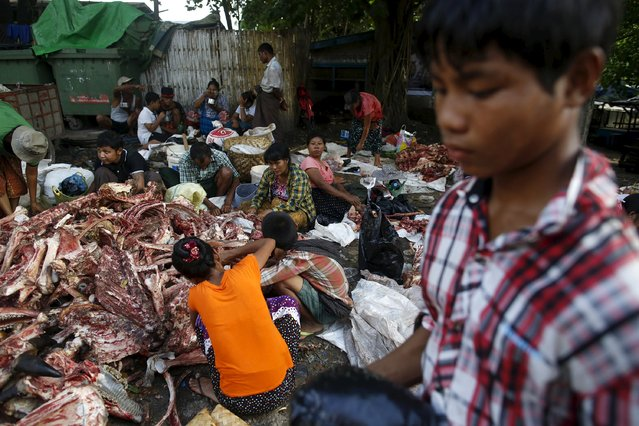 People remove meat from the bones of animals slaughtered for Eid al-Adha after they have been discarded at a garbage dump in Yangon, Myanmar, September 25, 2015. (Photo by Soe Zeya Tun/Reuters)
