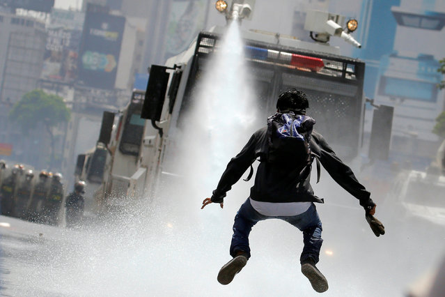 """A demonstrator jumps away from a jet of water released from a riot security forces vehicle during a rally against Venezuela's President Nicolas Maduro in Caracas, Venezuela, May 26, 2017. Carlos Barria: """"Weeks into protests against Venezuela's President Nicolas Maduro, I landed in Caracas to reinforce our Reuters team coving the chaos. The protests had fallen into a routine. Every day around 10am – 11am protesters gathered around Altamira Plaza and started to march towards the downtown area where a cluster of government buildings are located. Protesters walked along a main highway and riot police would intercept them to contain the crowd. Clashes erupted when they met, with tear gas and water cannons were used to disperse the protesters. On May 26, a young student walked towards a water cannon wearing a backpack, as if he had just come out of class. As he got closer, the riot police turned the water canon directly on him. Then, the student began jumping and dodging, trying to avoid the blast of water. He looked almost as if he were dancing in the rain"""". (Photo by Carlos Barria/Reuters)"""