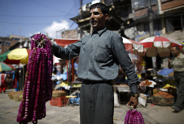 A street vendor sells garlands that are used for worship during the Tihar festival, also called Diwali, in Kathmandu October 20, 2014. (Photo by Navesh Chitrakar/Reuters)