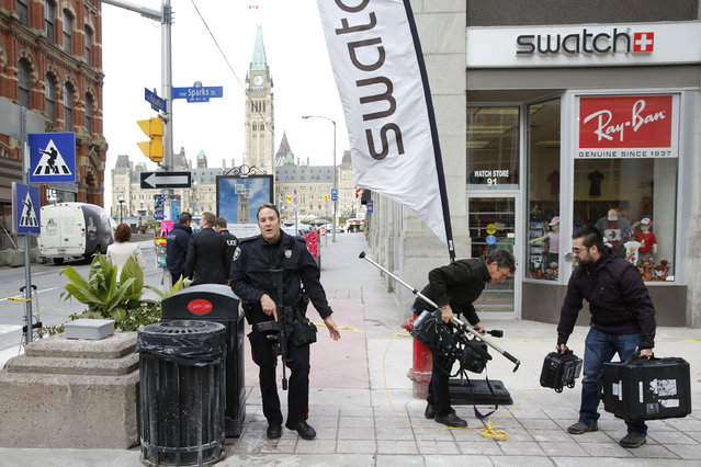 An Ottawa police officer attempts to clear people from an area on Metcalfe Street following shootings in downtown Ottawa October 22, 2014. (Photo by Blair Gable/Reuters)