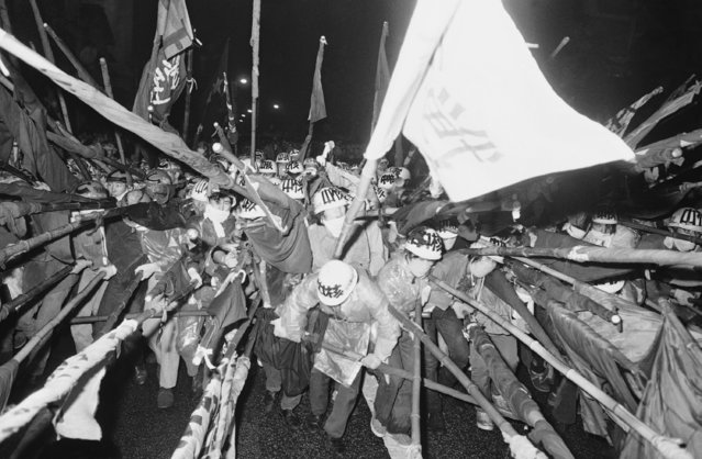 Armed with bamboo poles and protected with hard hats, a massed group of Japanese students surge forward to begin a demonstration in Tokyo on September 30, 1971.  Their protest was against terms for the return of Okinawa from U.S. to Japanese control. (Photo by AP Photo)