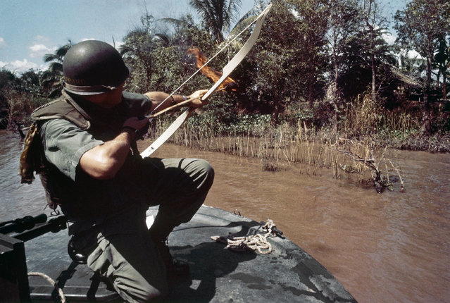 Tactics reminiscent of the early American frontier days are now being used in Vietnam. Lieutenant Commander Donald D. Sheppard, UBN, of Coronado, California, aims a flaming arrow at a bamboo hut concealing a fortified Viet Cong bunker on the banks of the Bassac River, Vietnam on December 8, 1967. (Photo by AP Photo)