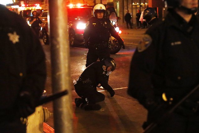 An injured police officer is seen on the ground after being hit by a glass bottle as revellers celebrate in the Mission District, in San Francisco, California October 29, 2014. (Photo by Stephen Lam/Reuters)