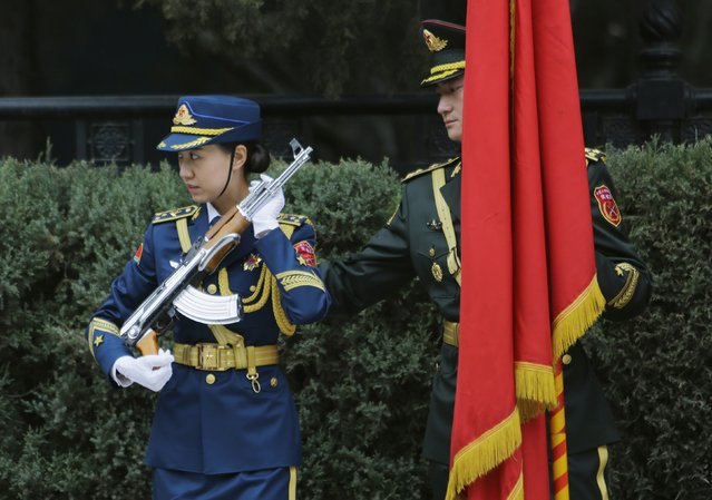 A member of an honour guard adjusts the gun strap of his female compatriot ahead of a welcoming ceremony for Afghanistan's President Ashraf Ghani Ahmadzai outside the Great Hall of the People, in Beijing, October 28, 2014. (Photo by Jason Lee/Reuters)