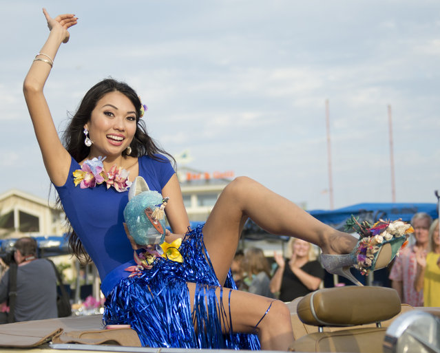 """Miss Hawaii Allison Chu waves to the crowd as she holds one of her shoes during the 2017 Miss America pageant """"Show Us Your Shoes"""" parade Saturday, September 10, 2016, in Atlantic City. (Photo by Chris Szagola/AP Photo)"""