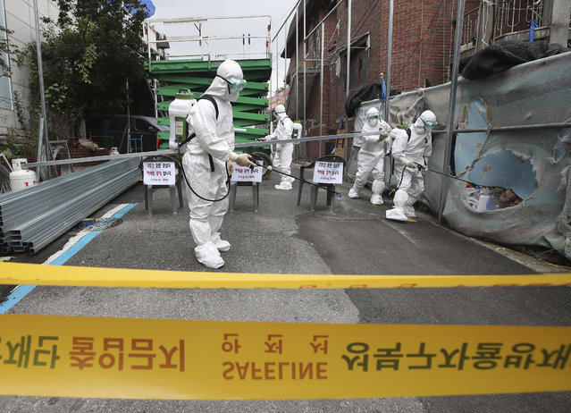 Public officials disinfect a church as a precaution against the coronavirus in Seoul, South Korea, Friday, August 14, 2020. South Korea reported over 100 new virus cases Friday, one of its biggest daily jumps in months, as officials express concerned that infections are getting out of control in cities as people increasingly venture out in public. (Photo by Han Jong-chan/Yonhap via AP Photo)