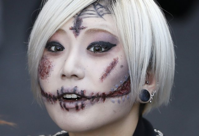 """A participant dressed as a zombie marches during a Halloween event to promote the U.S. TV series """"The Walking Dead"""" at Tokyo Tower October 31, 2013. (Photo by Issei Kato/Reuters)"""