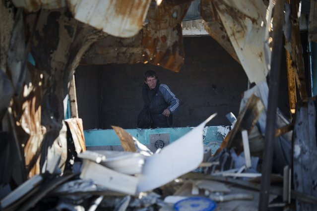 In this photo taken on Tuesday, October 28, 2014, a man roams in a bombed out street market near the train station in the town of Donetsk, eastern Ukraine. (Photo by Dmitry Lovetsky/AP Photo)