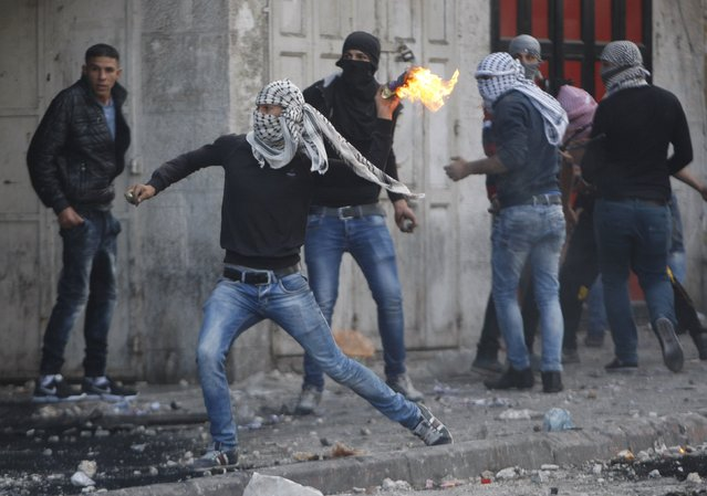 A masked Palestinian throws a molotov cocktail at Israeli troops during clashes in the West Bank city of Hebron October 9, 2015. (Photo by Mussa Qawasma/Reuters)